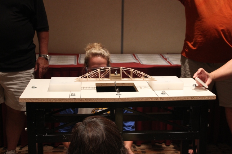A science olympiad coach tests the strength of her bridge.